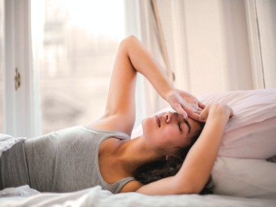 Energy draining activities to avoid - woman tired in bed