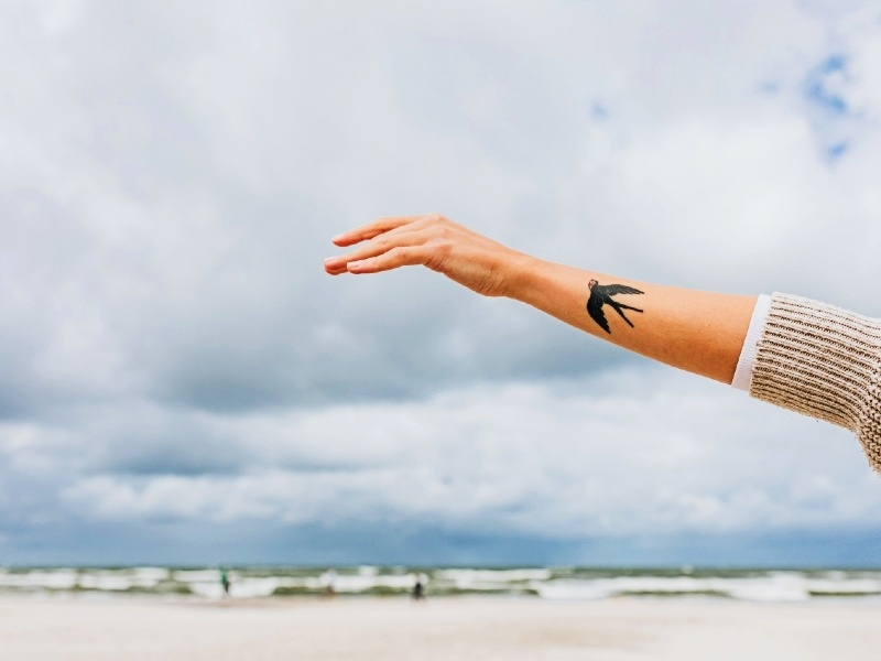 Daily affirmations list - a hand with a bird tattoo and clouds in the background