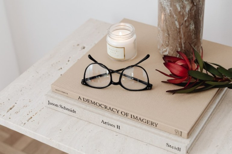 How to improve your mental well-being - a calming photo of books, sunglasses and a candle